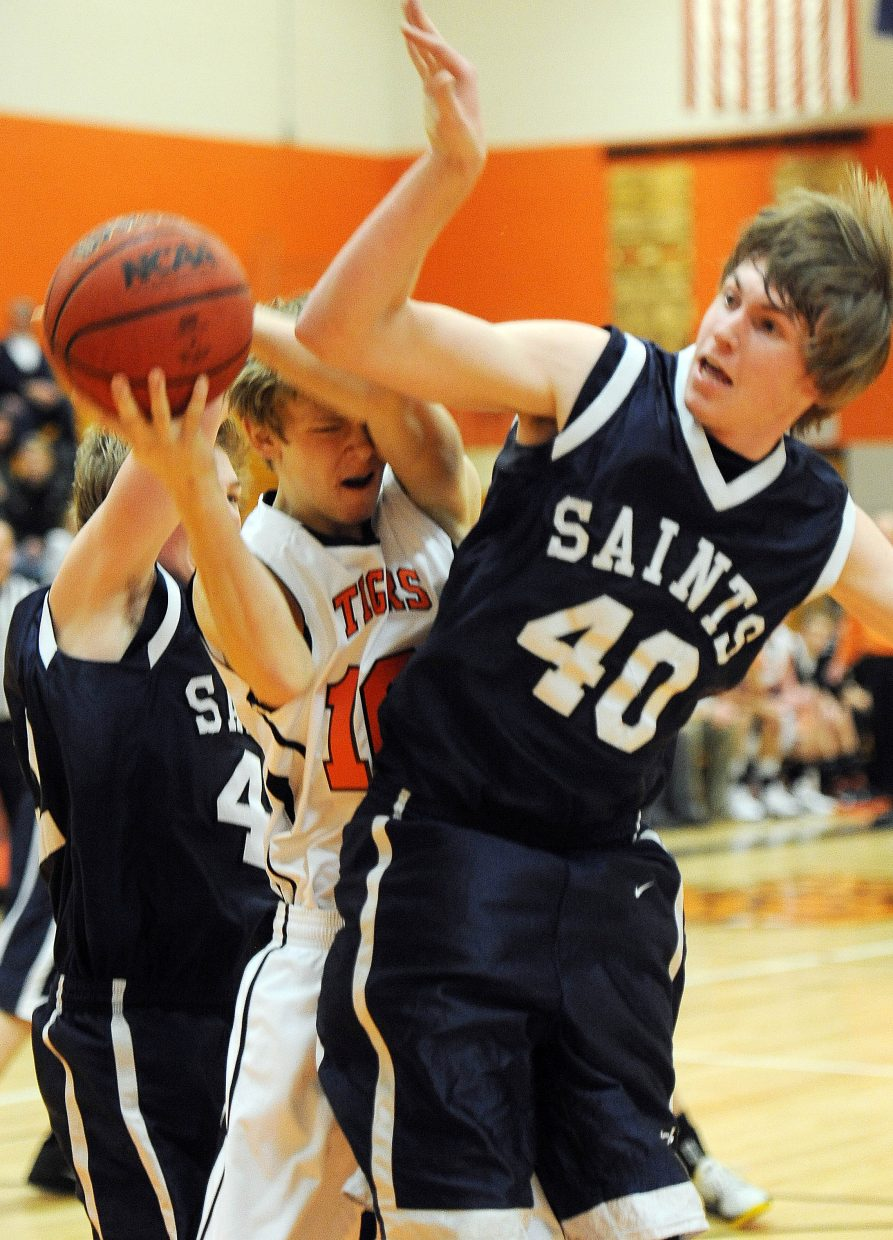 Hayden's Daniel Engle pulls a rebound down between Vail Christian's Kevin Boselli, 40, and another Saints player Saturday in the Tigers' 59-50 home victory.