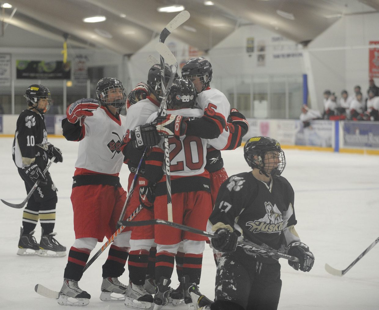 Members of the Steamboat Springs High School hockey team celebrate after a goal by sophomore Bobby Elliott during the first period of Saturday night's game against Battle Mountain High School.