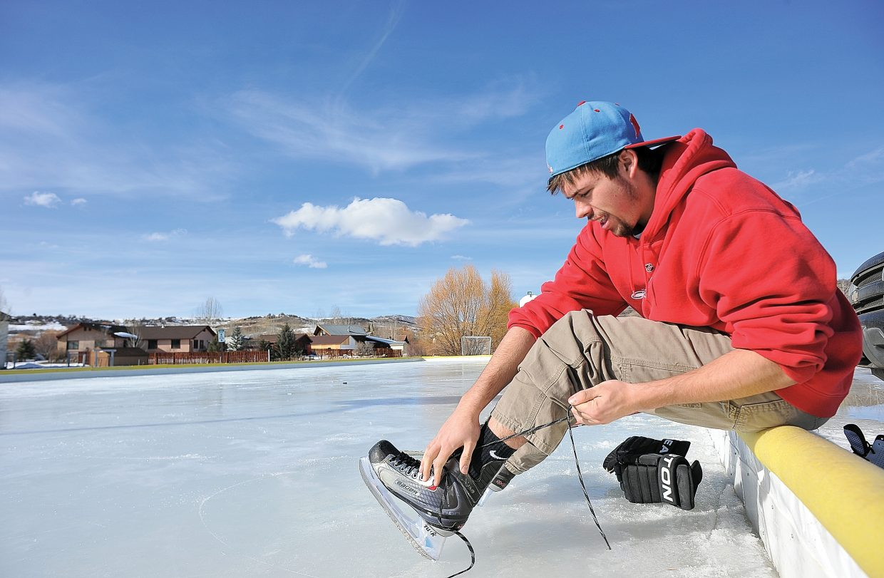 Mason Bates laces up his skates Tuesday afternoon before hitting the ice at the Steamboat II ice skating rink. Bates took advantage of the rink's ice to get out and enjoy the clear mountain sky and mild temperatures.