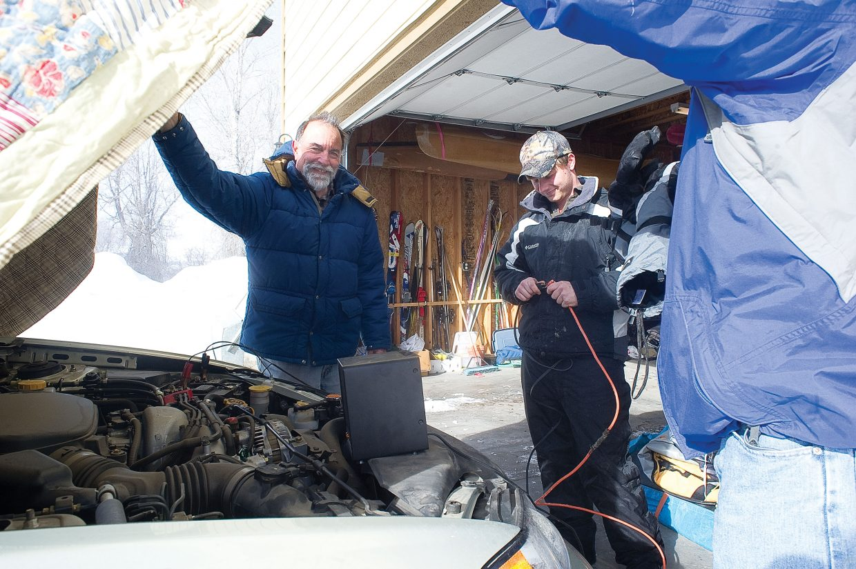 Getting the car started Wednesday morning proved to be a challenge for Fairview resident David Wallace, left. Wallace got a helping hand hooking his battery to a charger from J.P. Peacock.