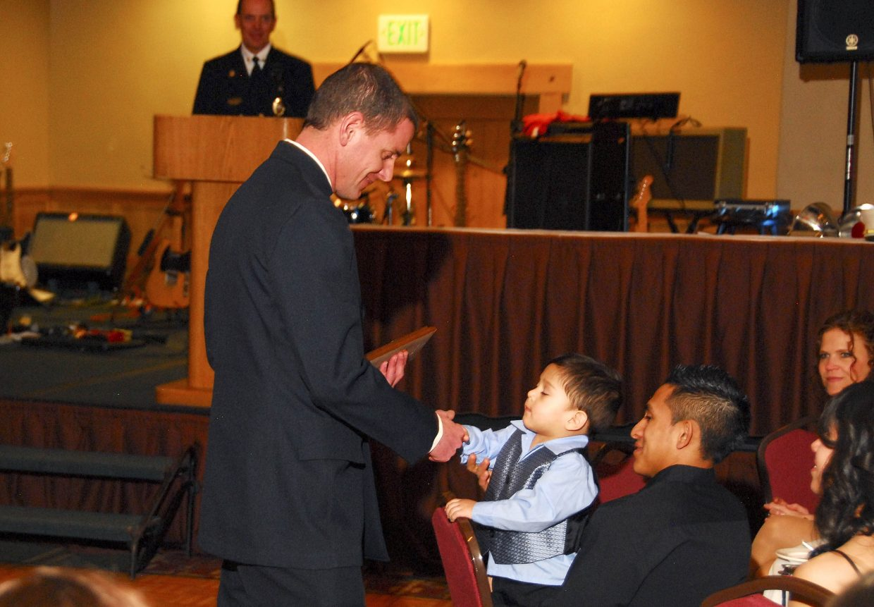 Steamboat Springs Fire Rescue firefighter Brian Shively shakes Edwin Rodriguez's hand during the Fireman's Ball on Saturday at the Sheraton Steamboat Resort. Shively helped save Edwin's life in June after the 14-month-old fell into Butcherknife Creek.