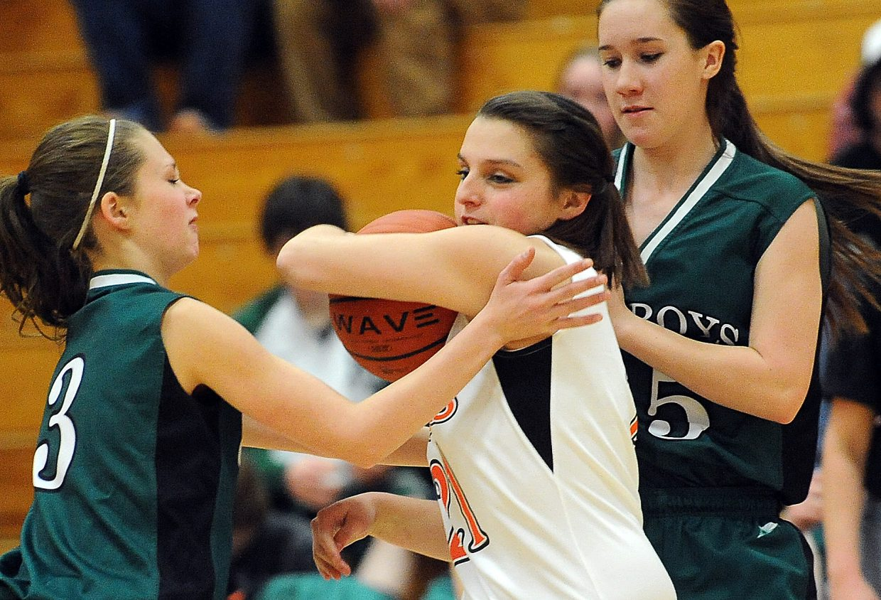 Hayden senior Jenn Bugg fends off Plateau Valley players after scooping up a steal in Friday's 63-36 win.