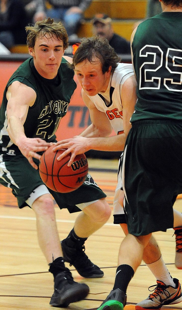 Hayden's Hunter Johnston tries to cut between a pair of defenders Friday against Plateau Valley.