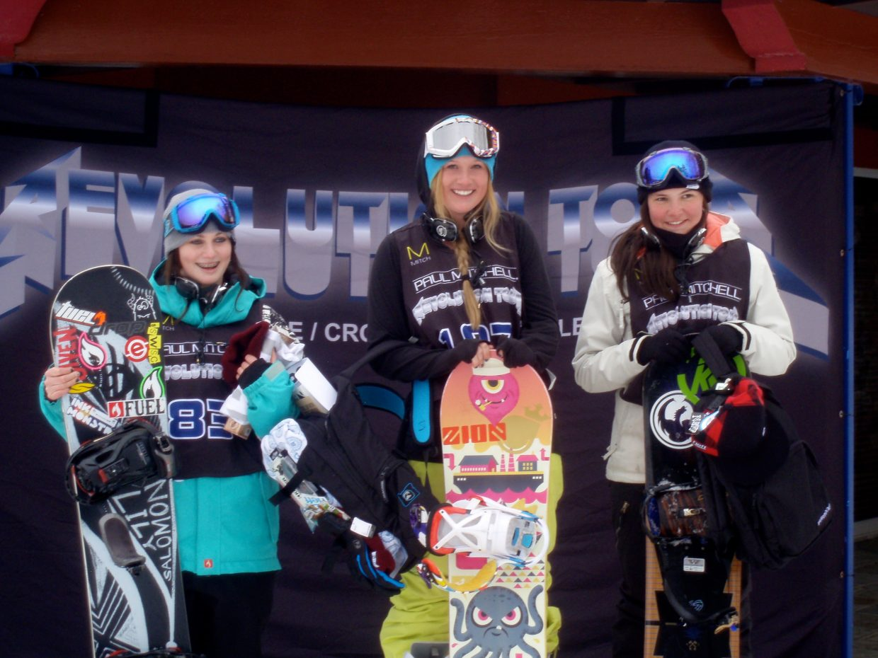 Haille Soderholm stands atop the women's slope-style podium at the Revolution Tour in Ostego, Mich. Lindsea Lumpkin, left, placed third.