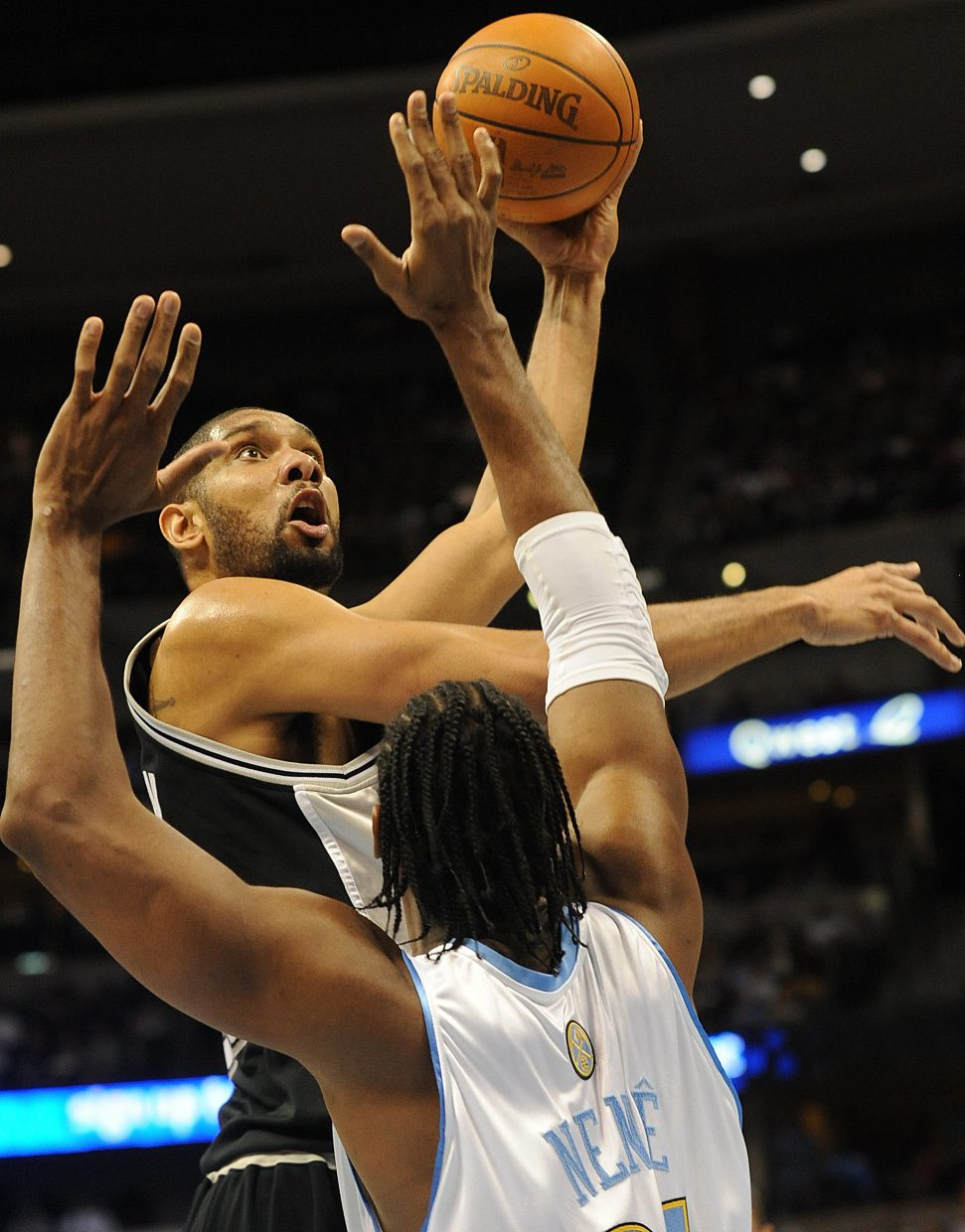 San Antonio's Tim Duncan lifts a shot of Denver's Nene on Thursday as the Spurs beat the Nuggets in Denver.
