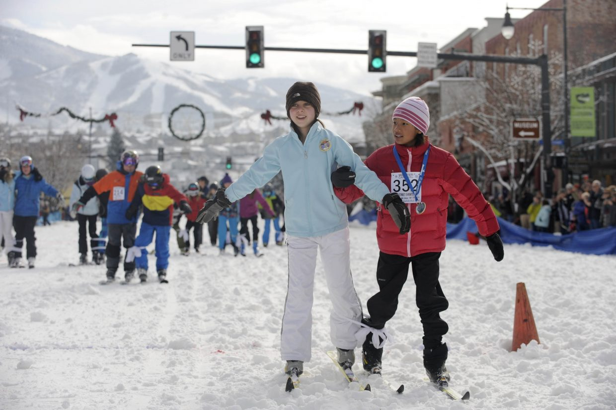 Ten-year-olds Katy Floyd, right, and Lauren Ehrlich compete in the three-legged race during the Winter Carnival street events Saturday.
