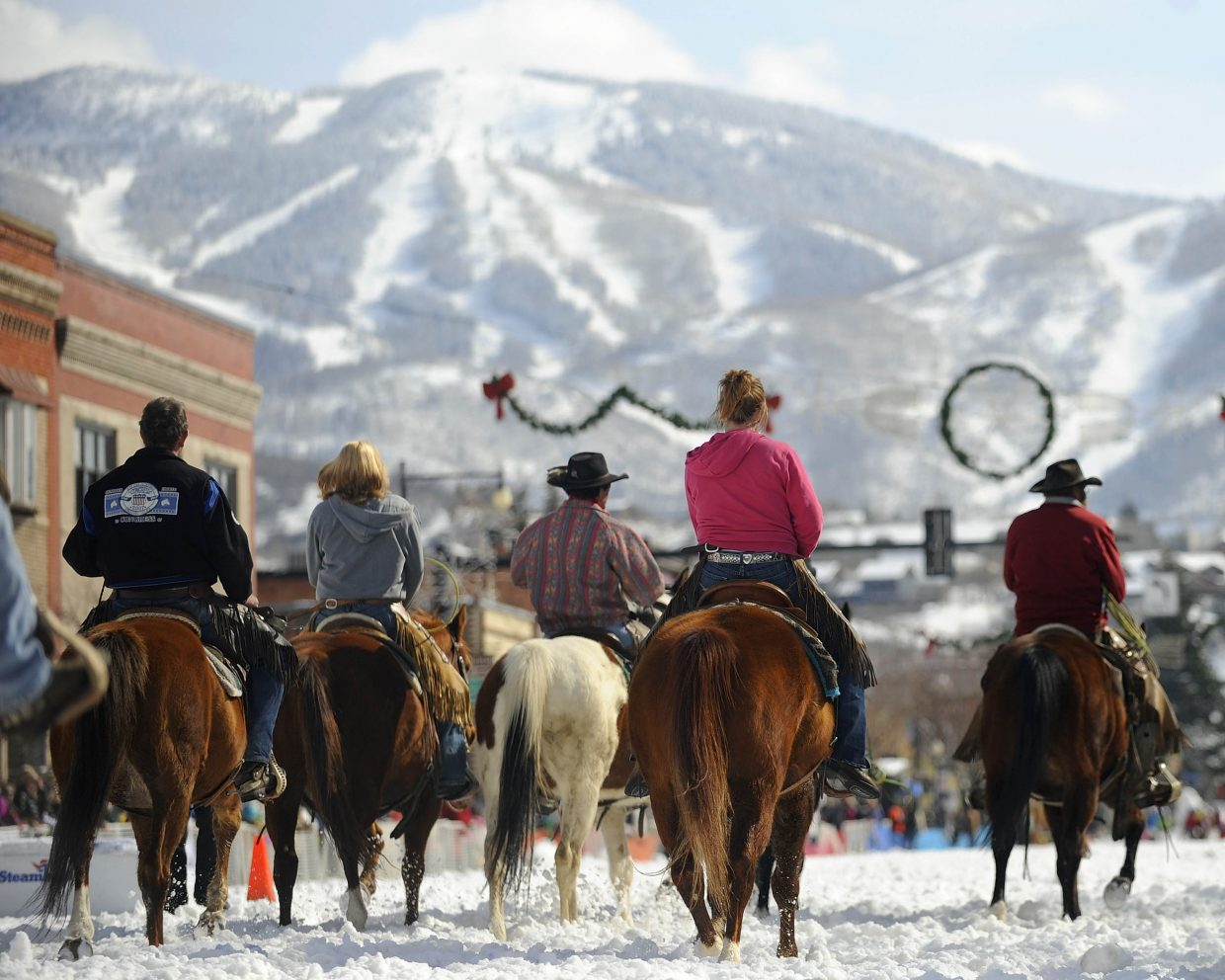 Horses walk down Lincoln Avenue during the Winter Carnival street events Saturday.