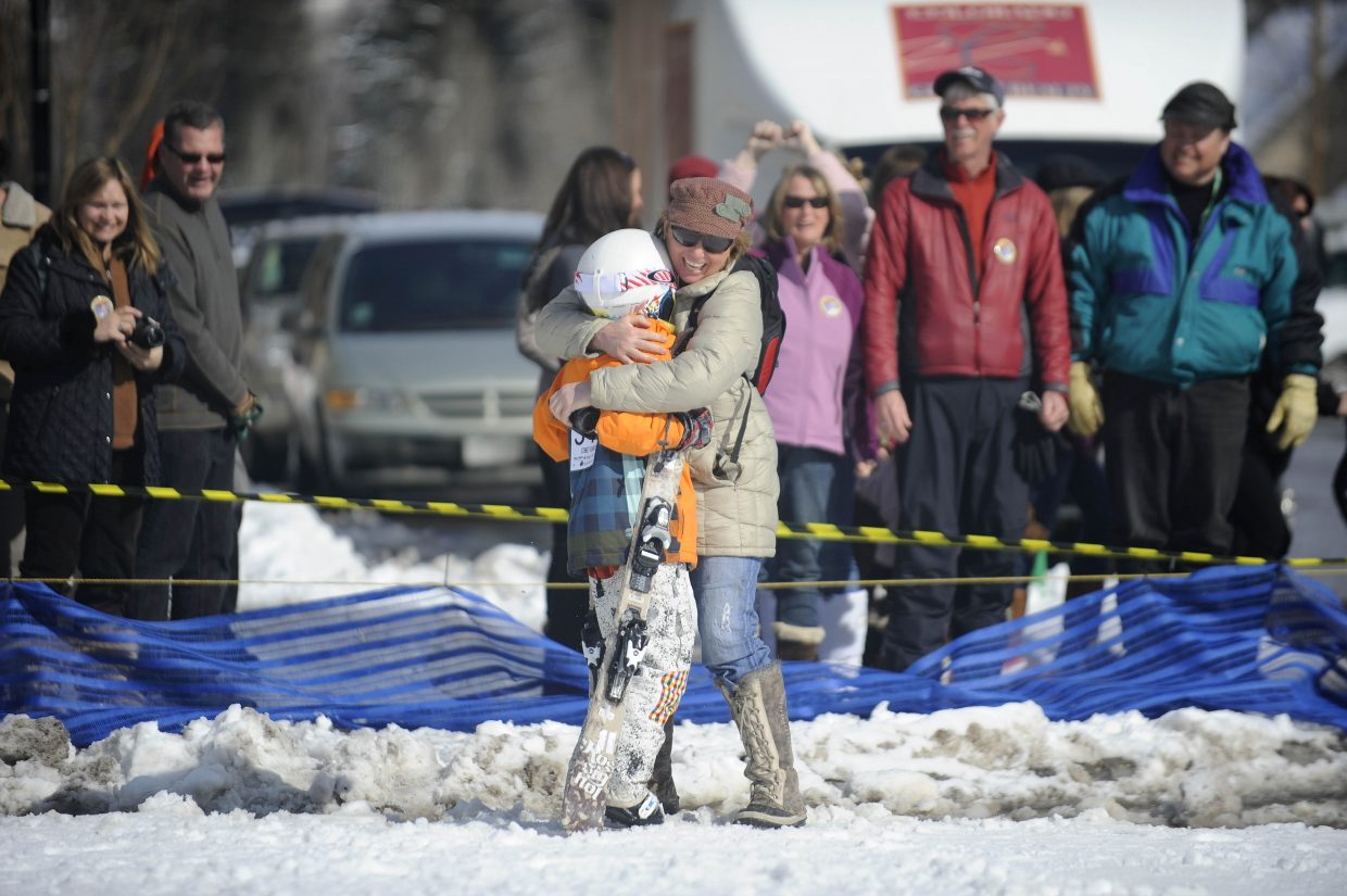 Michele Baxter hugs her son Liam after his jump in the donkey jump competition during the Winter Carnival street events Saturday.