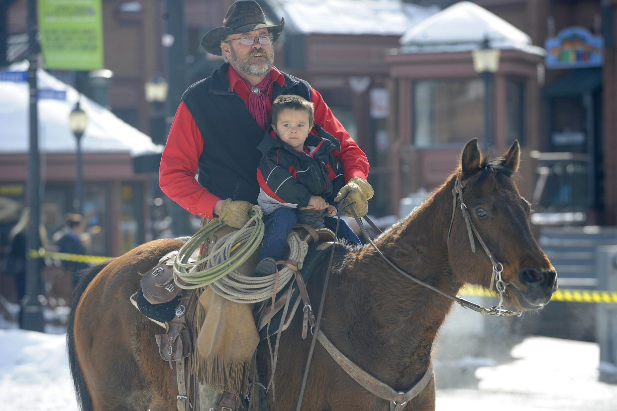 Doug Wheeler rides with his grandson William Rush during the Winter Carnival street events Saturday.