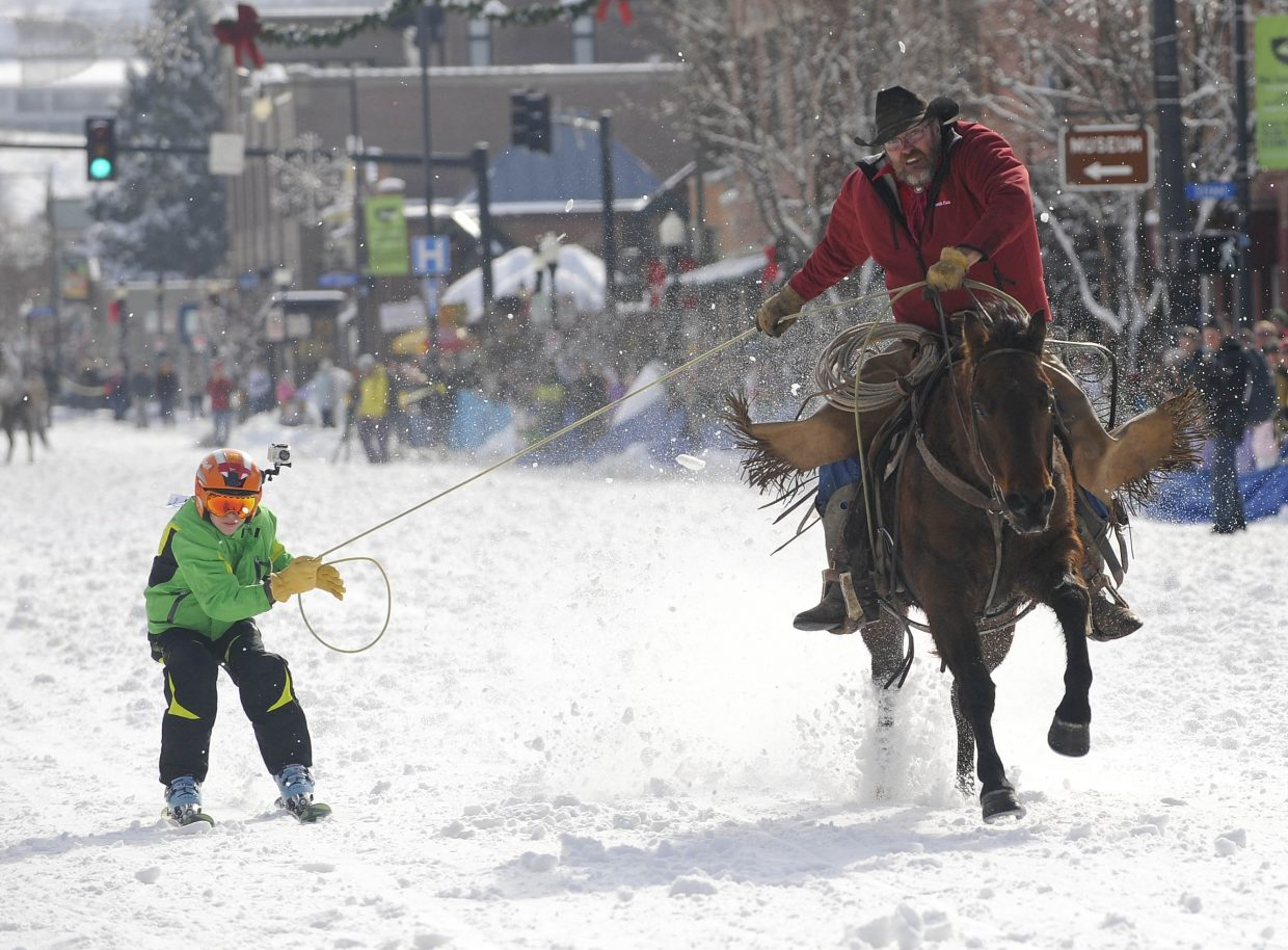 Doug Wheeler pulls Parker Temple during the Winter Carnival street events Saturday.
