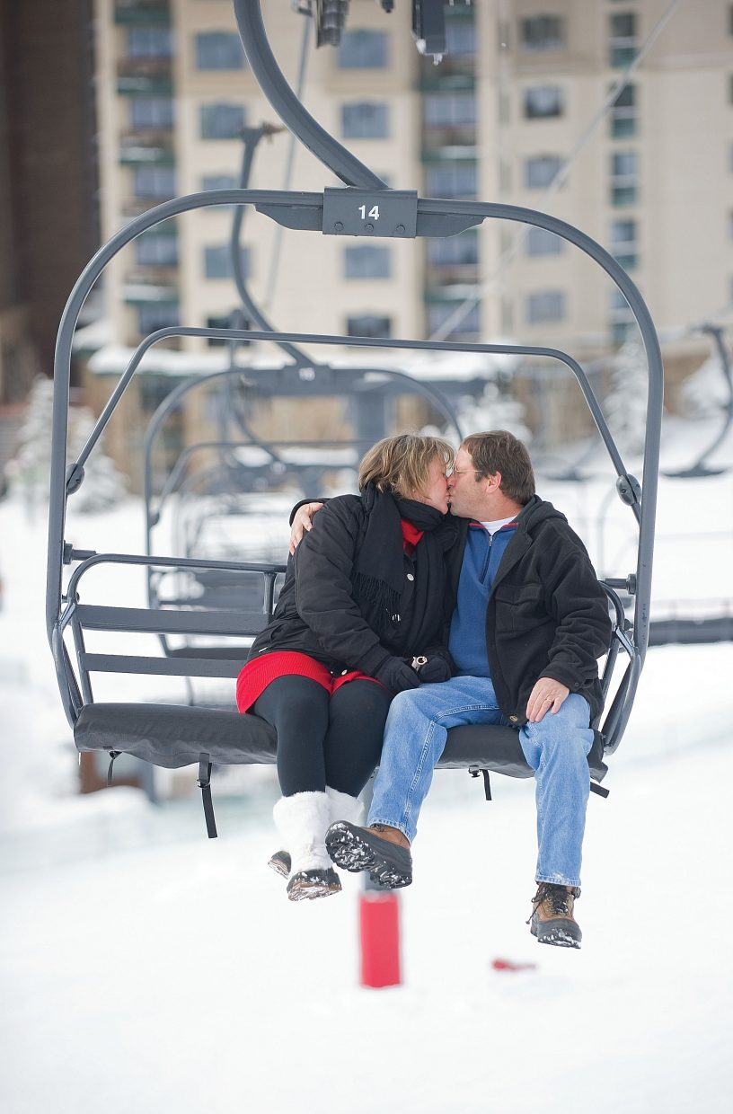Jill and Barry Limberg share a kiss while riding up the slopes of the Steamboat Ski Area on the Preview lift last week. The two said their were introduced while working as lift operators on Preview in 1986.