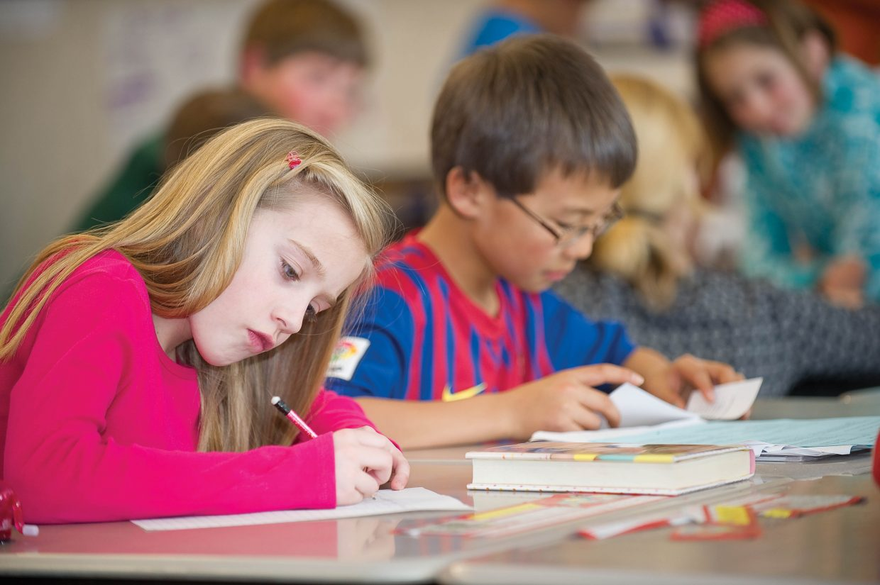 Fourth-grader Taylor Fieldind writes down ideas while working with classmate James Berntsen during a class project Monday at Soda Creek Elementary School.
