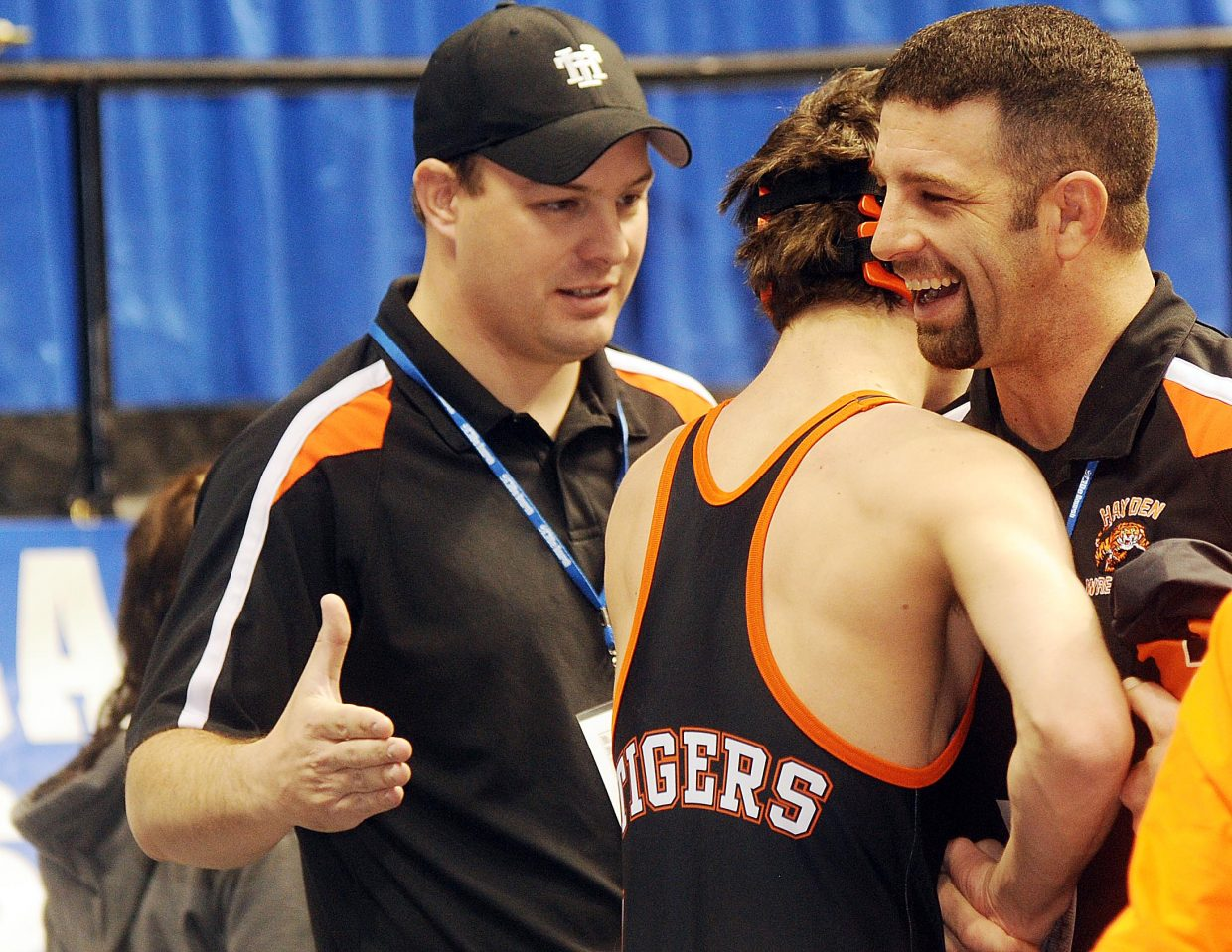 Hayden senior Scott Armbruster accepts congratulations from his coaches after winning his first match in four years at the state wrestling tournament.