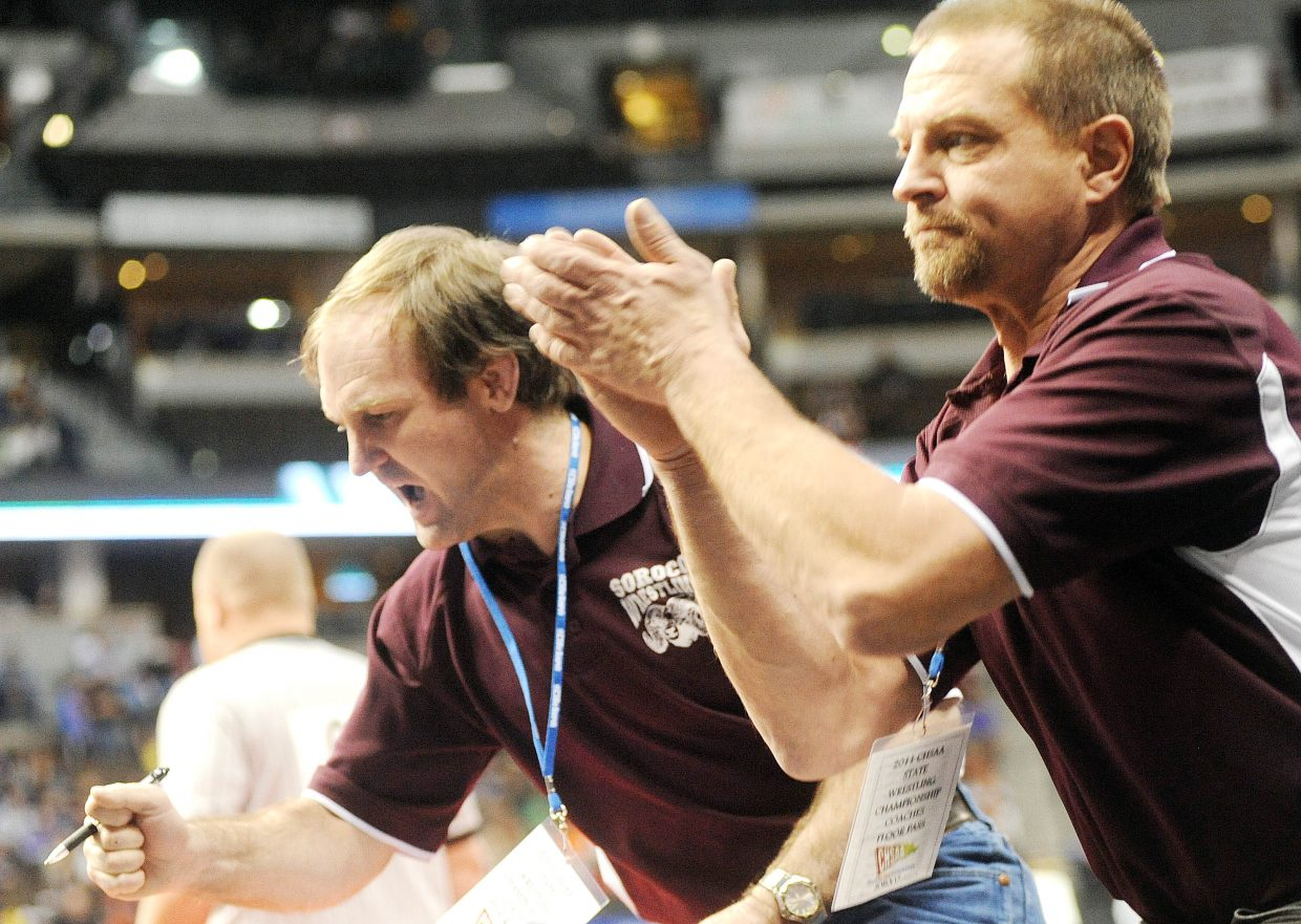 Soroco coaches Jay Whaley, left, and Travis Bruggink celebrate as Josh Baker earns a pin Friday at the state wrestling tournament in Denver.
