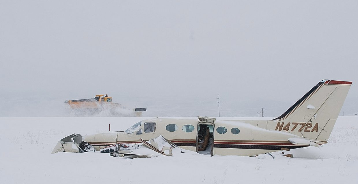 A runway plow passes behind the wreckage of a Cessna 414A that crashed just short of the runway at Yampa Valley Regional Airport in Hayden on Sunday afternoon.