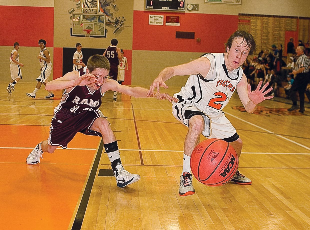 Hayden senior Hunter Johnston and Soroco junior Cody McCollum battle for a loose ball in the first half of Tuesday's district playoff game in Hayden.