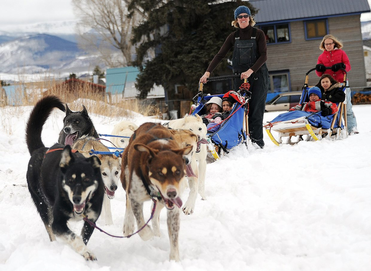 A team of dogs mostly composed of Iditarod finishers rounds a corner on a snowy field next to South Routt Elementary School on Wednesday. Tami Thurston offered rides to students, helping cap off lessons they'd been learning about the dogs and the race.