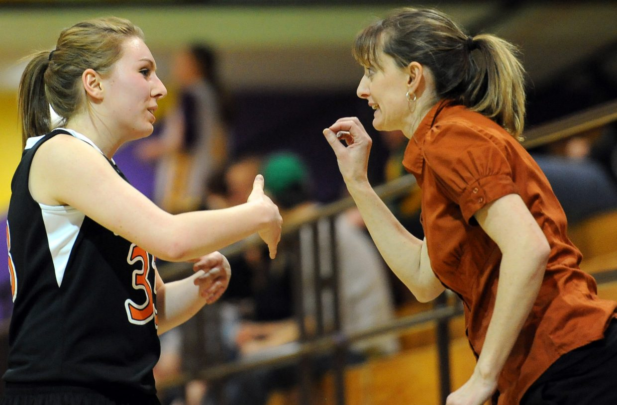 Hayden's Brette Frentress and Tigers' coach Michelle Wilkie talk strategy Friday at the district basketball tournament in Hayden.