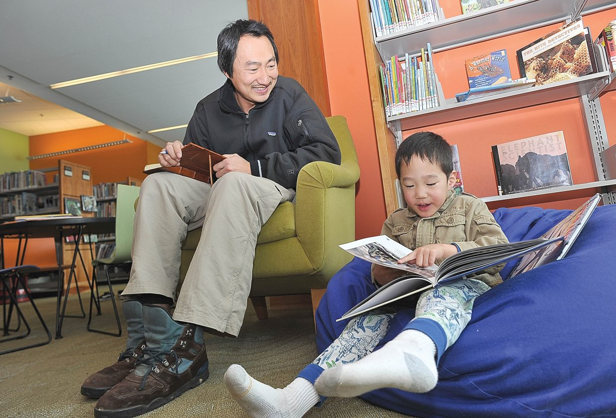 David Moon shares a moment with his 4-year-old son Elijah on Monday morning at Bud Werner Memorial Library.