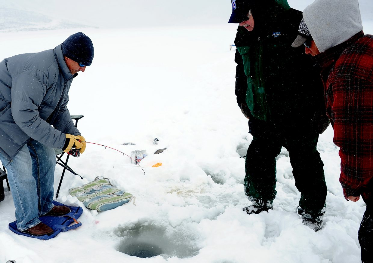 Eric Bonnett reels in a trout as Randy Brooks, center, and Steamboat Great Outdoors owner Kent Baucke wait to see what comes out of the hole in the Stagecoach Reservoir ice. Baucke began guiding ice fishing trips on the Routt County lake this winter.