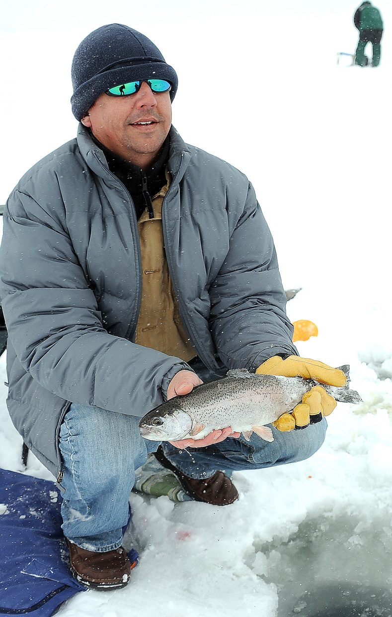 Eric Bonnett holds up his catch during a day of ice fishing at the Stagecoach Reservoir.
