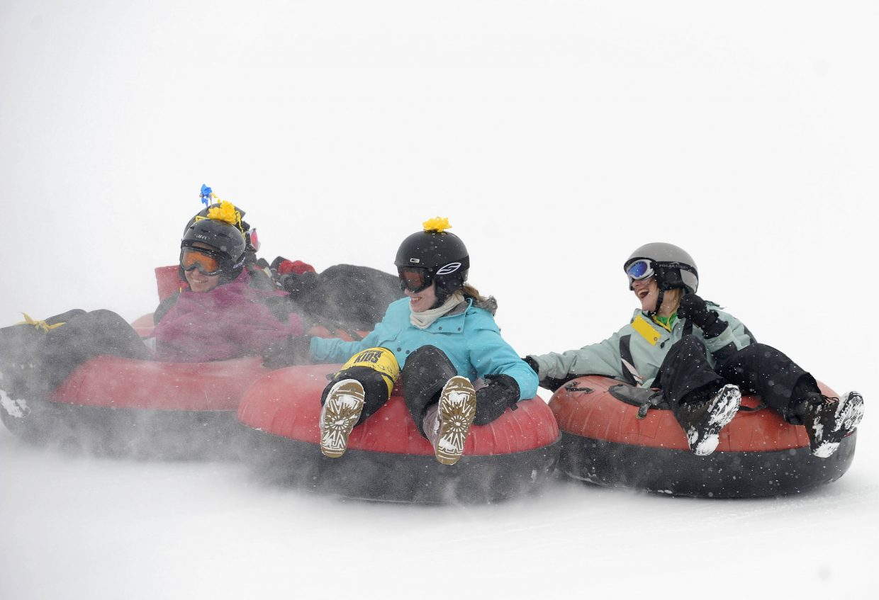 Children, from left, Emrene Sadek, of Texas; Katie Darr, of New York; and Tristan Hinshaw, of Texas, ride down the tubing hill at Saddleback Ranch.