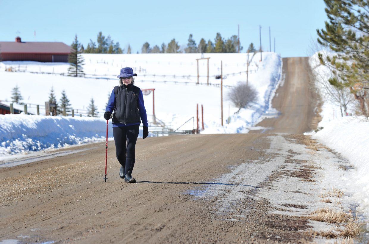 Rita Carlson walks along Routt County Road 33A on Thursday morning to get her mail. The warm temperatures have melted most of the snow from the roadway, but it isn't too muddy because the ground still is frozen in most places.