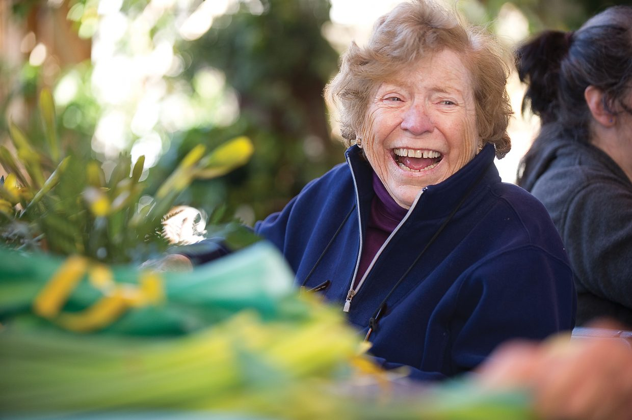 Volunteer Alice Lewis laughs while visiting with friends and wrapping daffodils Monday morning at Alpine Floral & Atrium in Steamboat Springs.