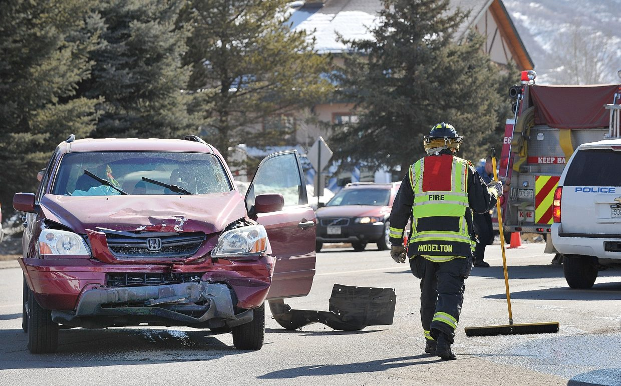 Steamboat Springs Fire Rescue firefighter Mike Middleton cleans debris from a two-car accident at Central Park Drive and Mount Werner Road on Wednesday morning after a police vehicle collided with a Honda Pilot after making a left turn onto Mount Werner Road. Two people in the Pilot were transported to Yampa Valley Medical Center.