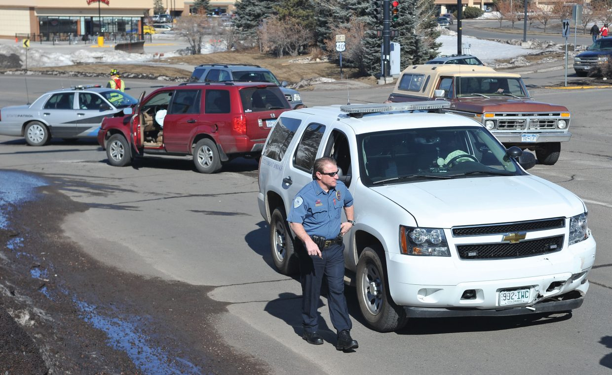 Steamboat police Capt. Jerry Stabile checks out a patrol car that was involved in an accident at Mount Werner Road and Central Park Drive on Wednesday morning. The police car driven by Steamboat police Sgt. Gerard Geis collided with the Honda Pilot in the background while attempting to make a left turn onto Mount Werner Road. Two people in the Pilot were transported to Yampa Valley Medical Center with minor injuries.