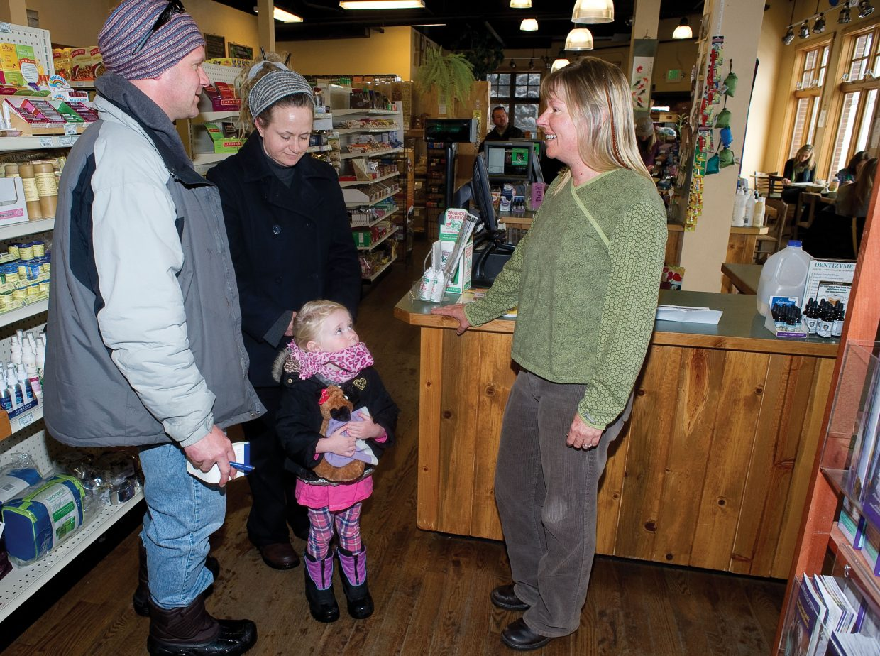 Bamboo Market owner Anne Halloran talks with local vendors Isaac and Renee Barber and their daugher Sobe.