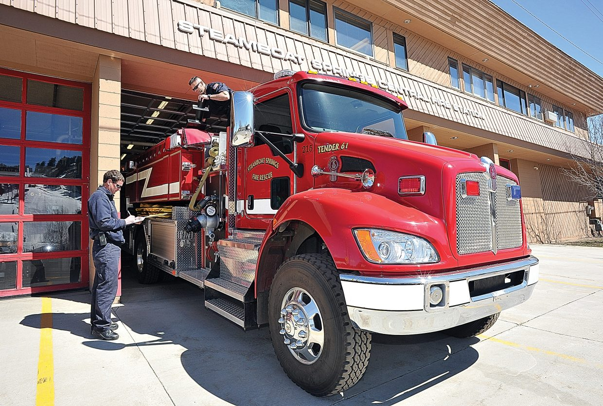 Steamboat Springs Fire Rescue firefighters Brian Shively, left, and Scott Hetrick inspect a fire truck at the Steamboat Springs Central Fire Station.