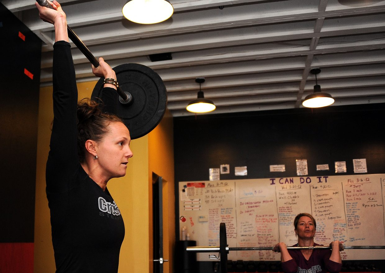 Ronni Collins, left, and Sarah Coleman lift during a workout Friday at Fusion Fit in Steamboat Springs. About a dozen athletes are working out at the gym, trying to make the CrossFit Games, an event established in 2007 that began getting play on ESPN this winter.