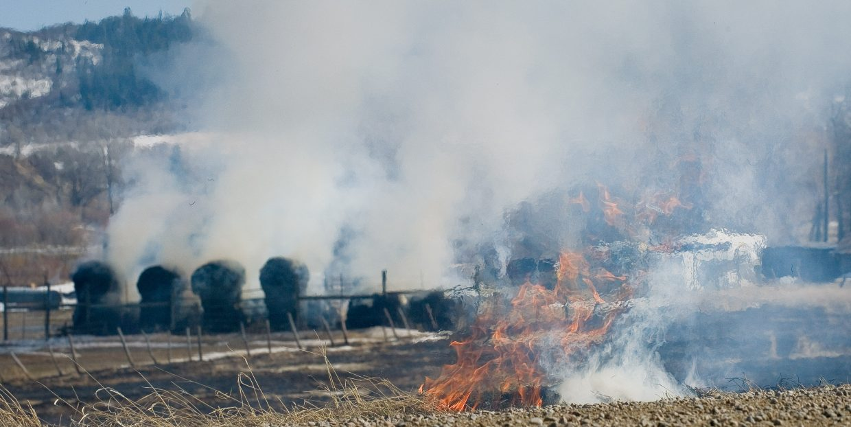 A haystack smokes behind flames from a wildfire that broke out Friday afternoon along Routt County Road 44. The fire was the result of a controlled burn that was pushed out of control by swirling winds and dry conditions. Members of Steamboat Fire Rescue responded and knocked the flames down, and the only real casualty was the nearby haystack, which caught fire and was destroyed.