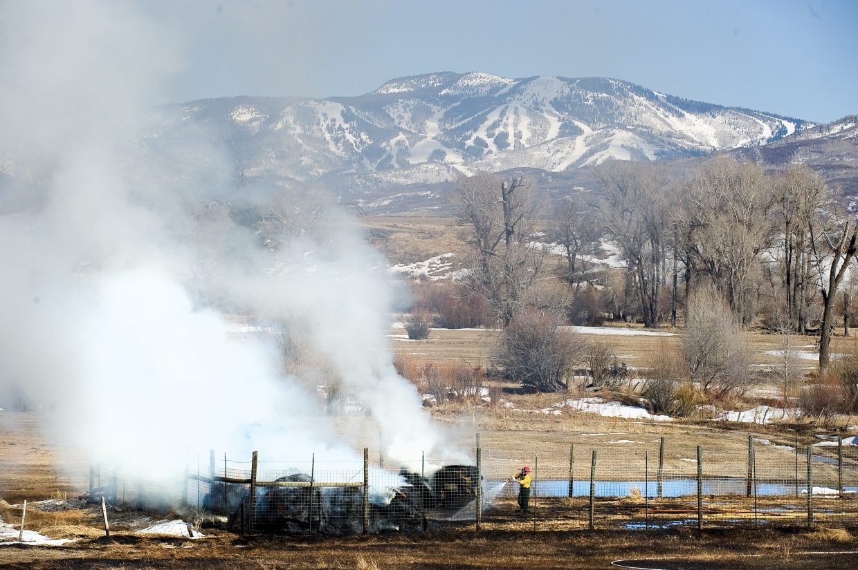 A firefighter from Steamboat Springs Fire Rescue knocks down flames in a haystack Friday afternoon on a ranch along Routt County Road 44. The fire was the result of a controlled burn that was pushed out of control by swirling winds and dry conditions. The only real casualty was a nearby haystack, which caught fire and was destroyed.