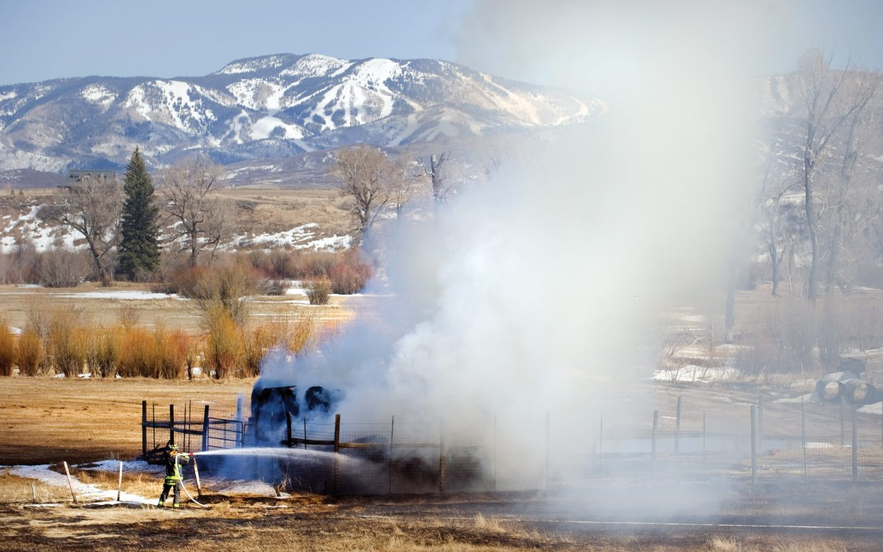 A firefighter from Steamboat Fire Rescue knocks down flames Friday afternoon on a haystack on a ranch along Routt County Road 44. The fire was the result of a controlled burn that was pushed out of control by swirling winds and dry conditions. The only real casualty was a nearby haystack, which caught fire and was destroyed.