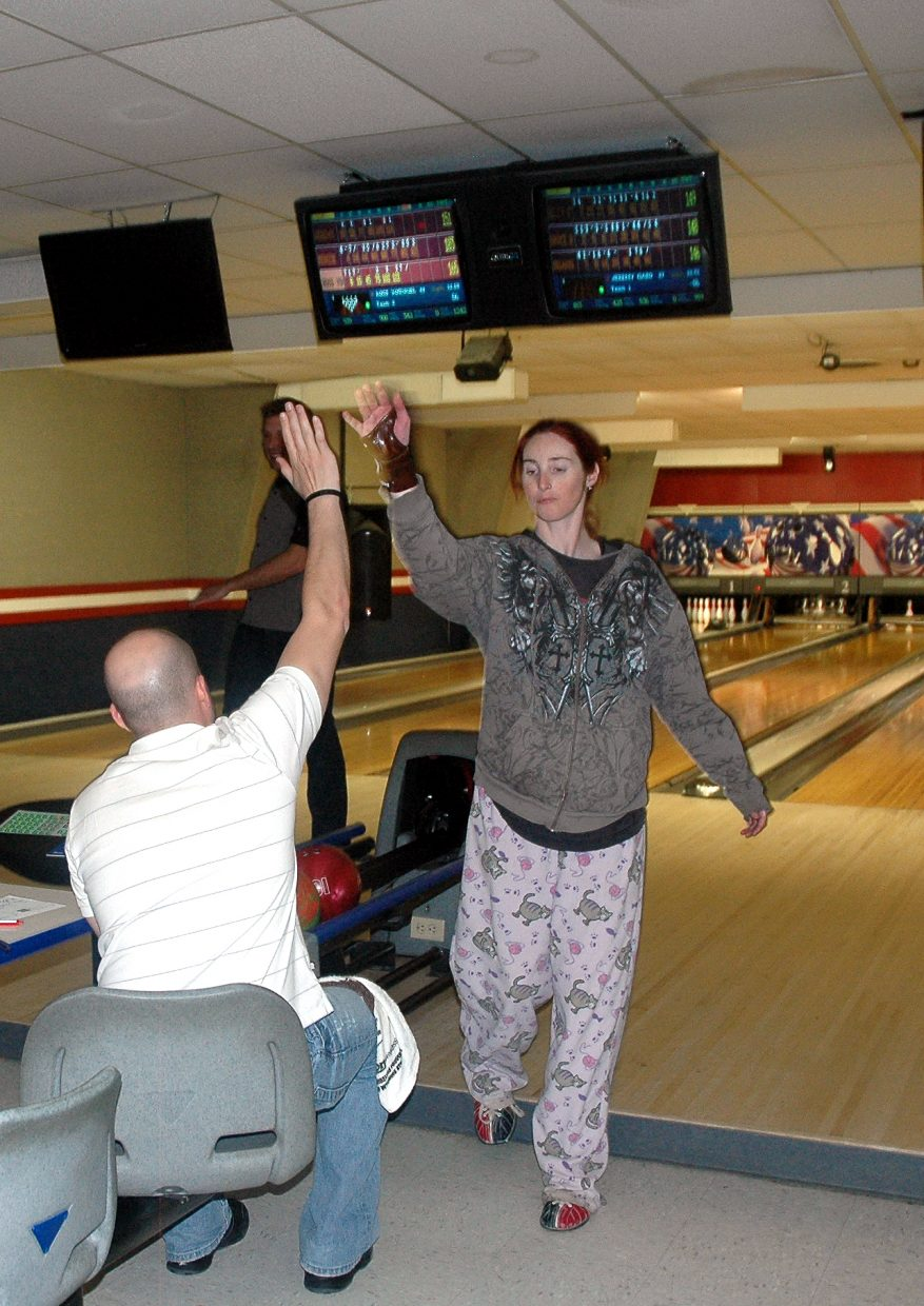 Horizons Specialized Services client Rhi Gifford high-fives a member of the opposing team during a Wednesday night bowling league at Snow Bowl.