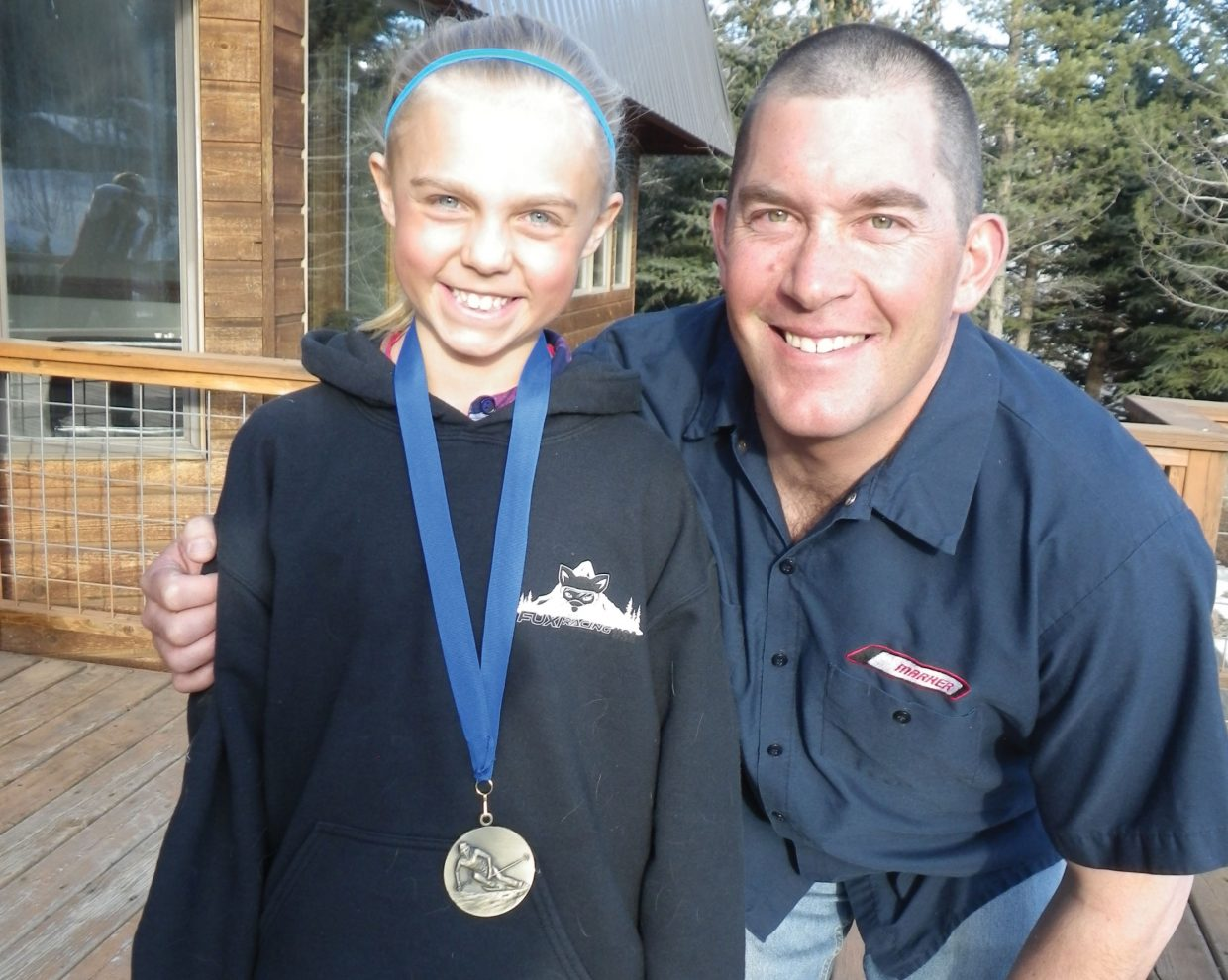 Coach Chris Puckett, sporting a new hairdo, poses for a photo with Riley Smith who won the girls slalom race at the J5 Rocky Mountain Division Finale on March 11 in Powderhorn. Riley got a medal for her performance and the chance to shave her coach's head, as well.