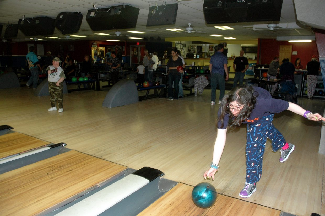 Misty Garcia, right, aims down the lane at Snow Bowl as Bruce Rule celebrates his roll. Both are clients of Horizons Specialized Services.