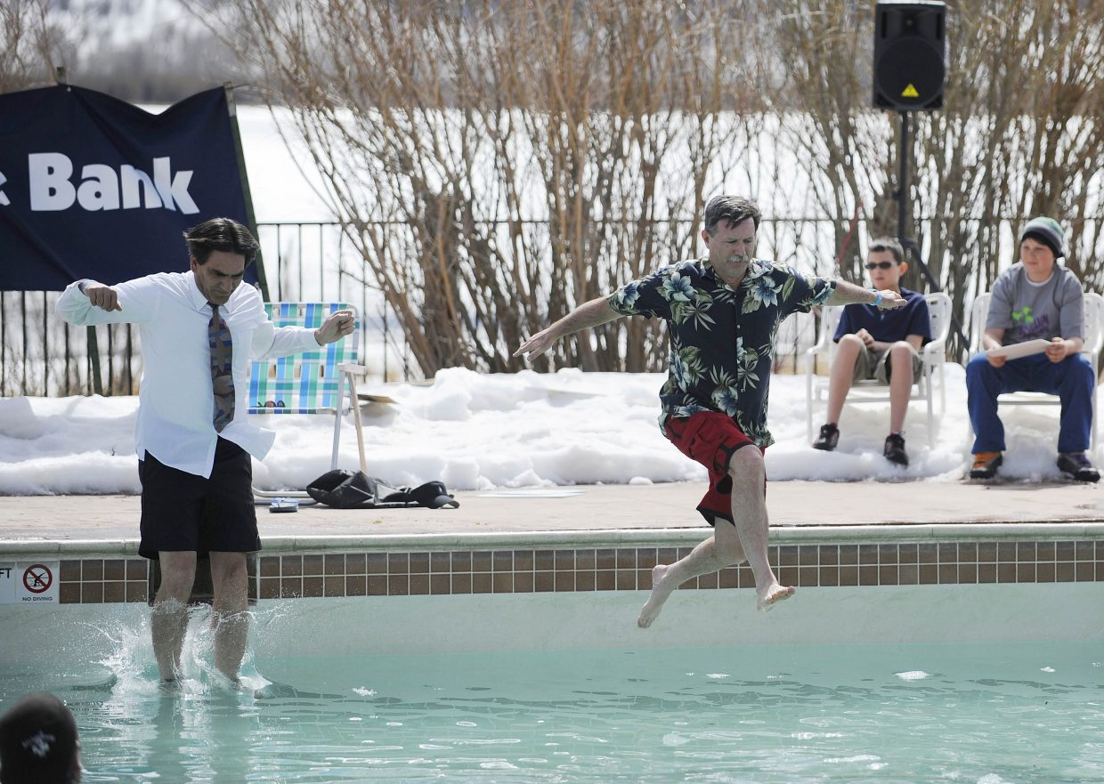 Retiring Yampa Valley Medical Center Chief Executive Officer Karl Gills, right, and incoming CEO Frank May jump into the near-freezing waters at Catamount Ranch & Club during Saturday's Penguin Plunge.