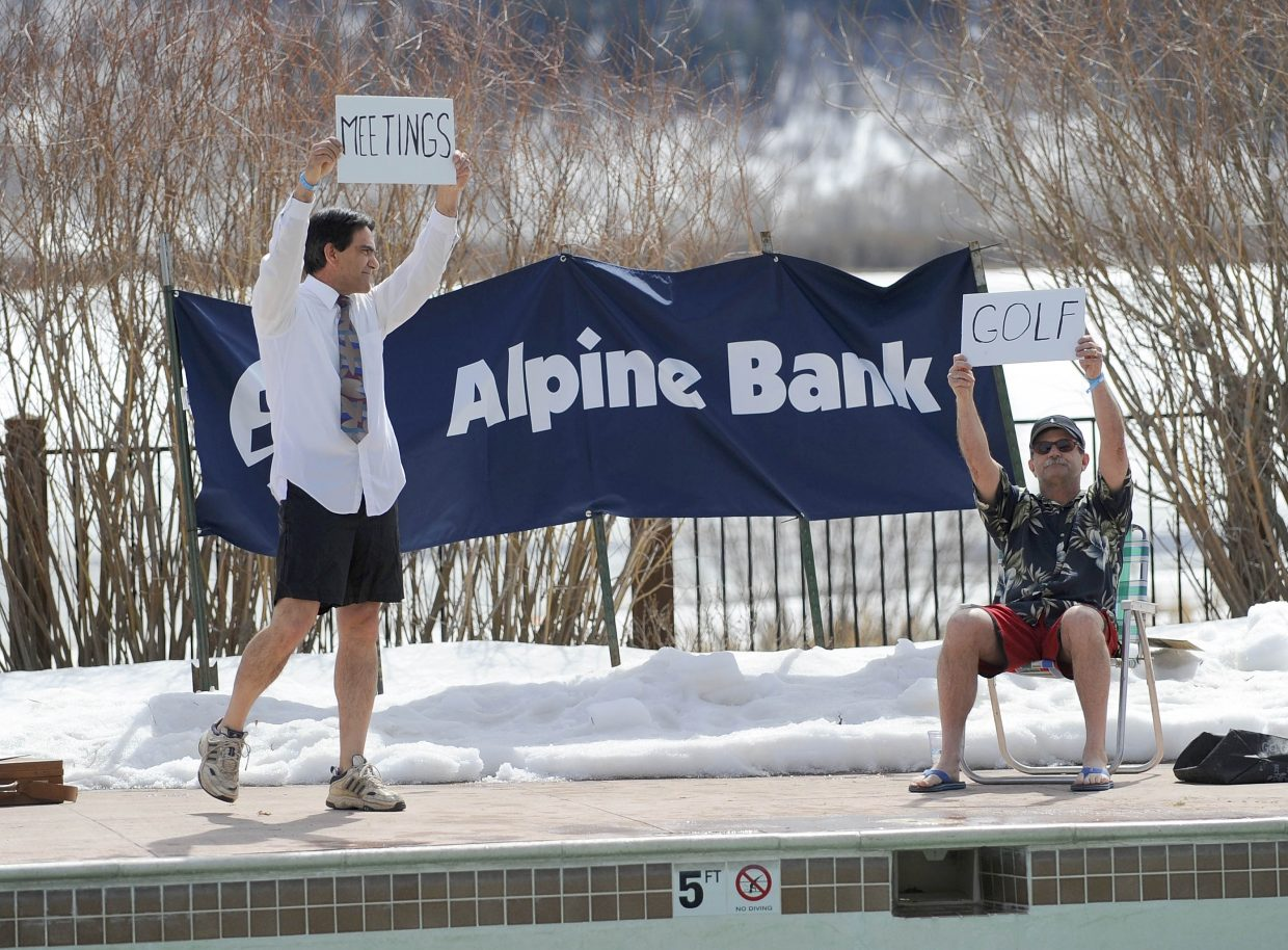 Retiring Yampa Valley Medical Center Chief Executive Officer Karl Gills, right, and incoming CEO Frank May hold up signs to illustrate their futures during the ninth annual Penguin Plunge on Saturday at Catamount Ranch & Club.