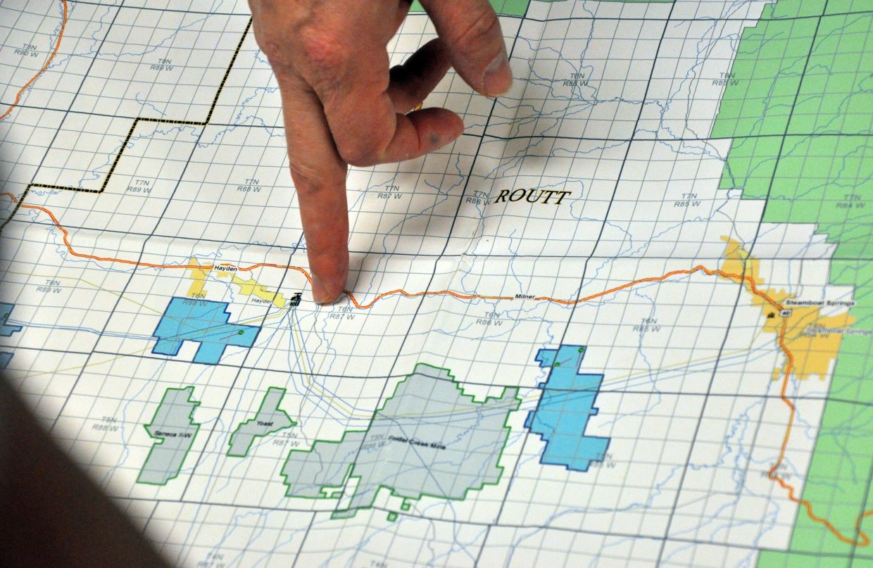 Matt Holman, Shell Oil's exploration project manager for Northwest Colorado, points to proposed drilling sites (pinpointed in blue) on a map of Routt and Moffat counties Tuesday night in Hayden. Shell Oil hosted an open house to share their exploration plans with the public.