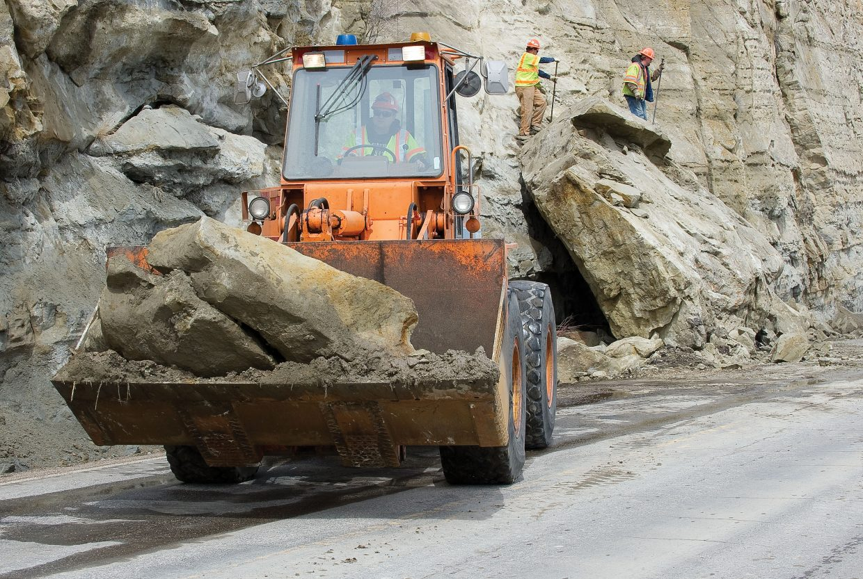Colorado Department of Transportation employee Chris Miller uses a front-end loader to remove parts of a rock that slid onto U.S. Highway 40 on Monday morning. The rocks struck two westbound vehicles and closed the road for two hours. One lane of the road was reopened as crews had to use explosives to break up the rock before it could be removed.