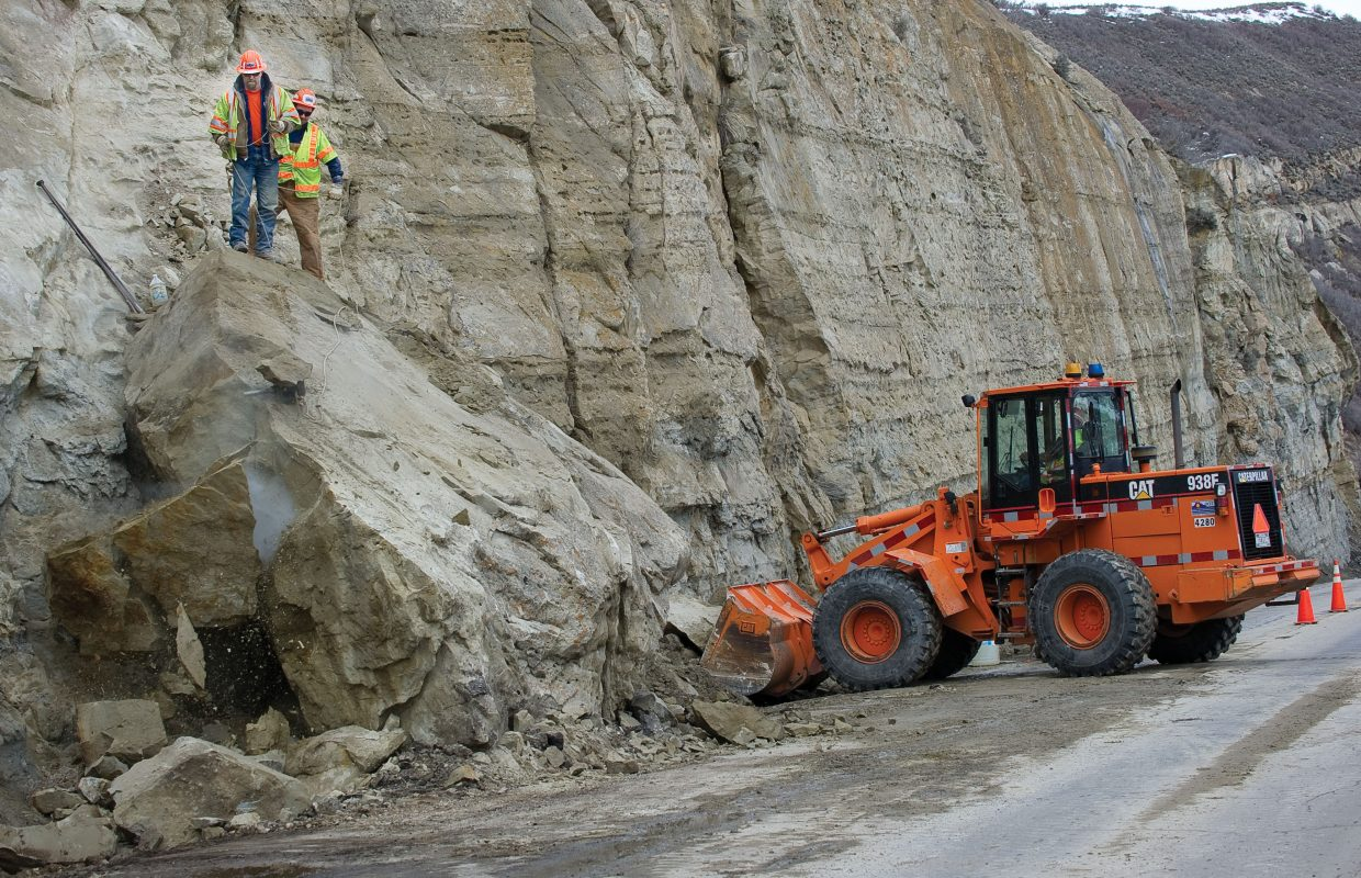 Tim Dickerson, front, and Andy Meadow use a blast cap to break a large rock into smaller pieces as Colorado Department of Transportation cleaned up a rockslide on U.S. Highway 40 on Monday afternoon. The slide, which happened at about 8 a.m., closed the highway for more than 2 hours. The highway was limited to one lane for most of the day as crews worked to clean up a large section of rock that had fallen on to the road.