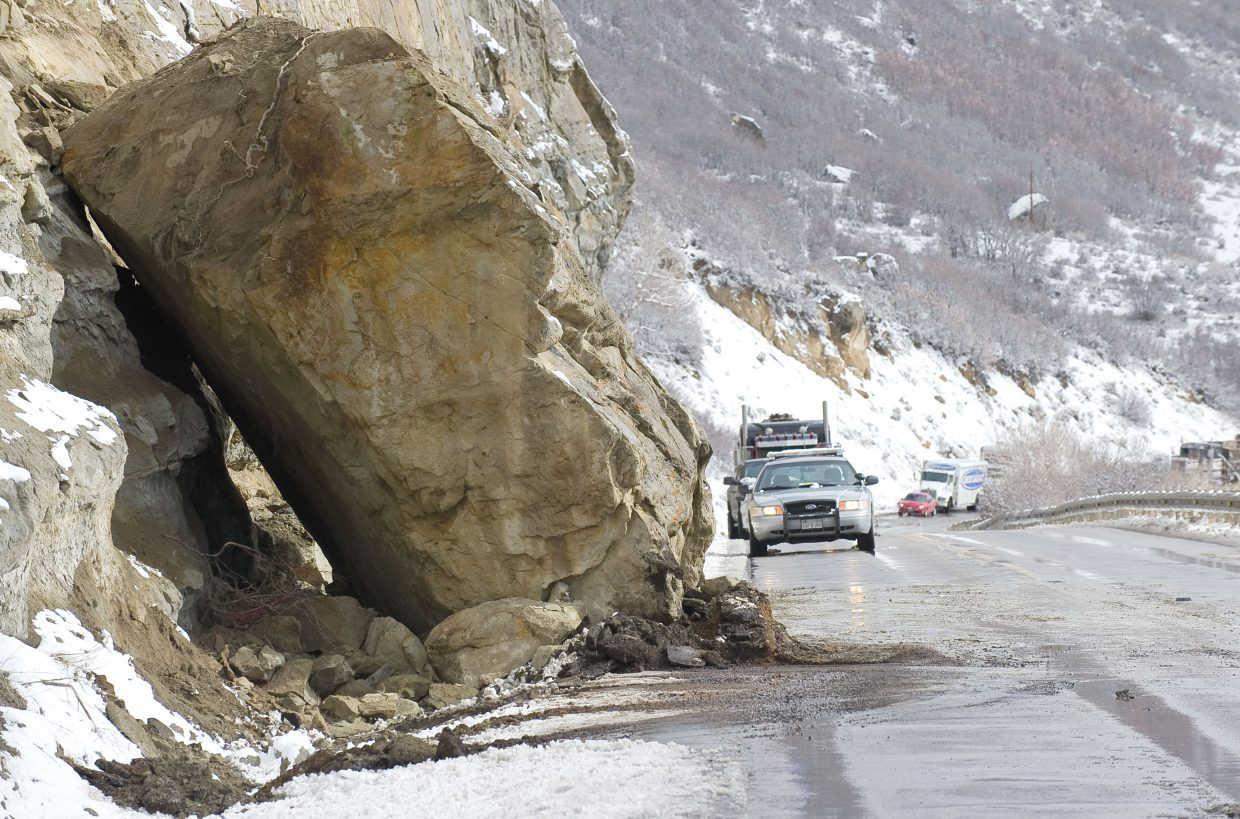 A Colorado State Patrol car sits behind a 15-foot-by-20-foot boulder that broke loose along U.S. Highway 40 between Hayden and Steamboat Springs on Monday morning. Two westbound vehicles were caught by the slide, and a passenger in a truck was transported to Yampa Valley Medical Center with non-life threatening injuries.