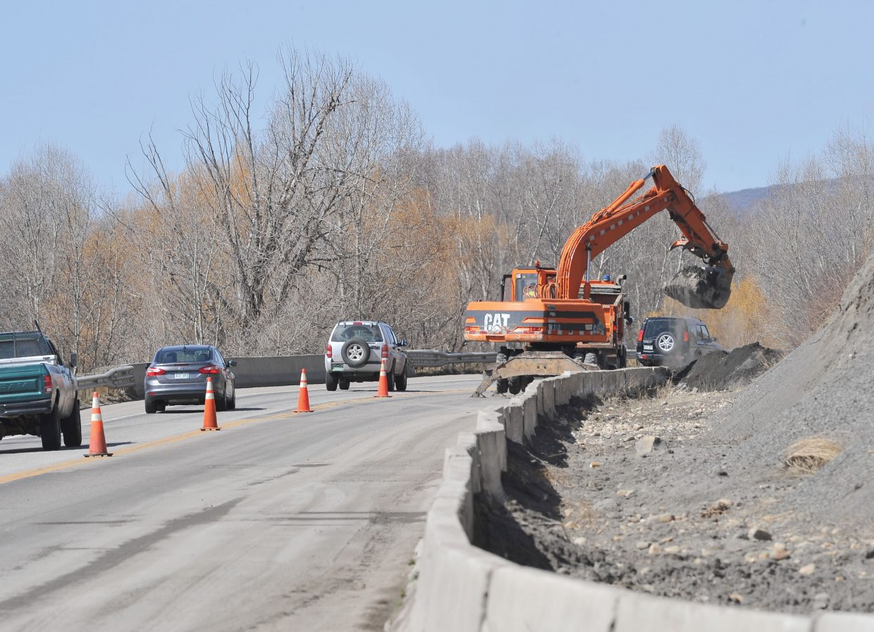Traffic passes a Colorado Department of Transportation excavator Wednesday afternoon as it works along U.S. Highway 40 near Riverside Plaza. The crews were cleaning areas where dirt, rocks and mud have slipped behind the barriers.