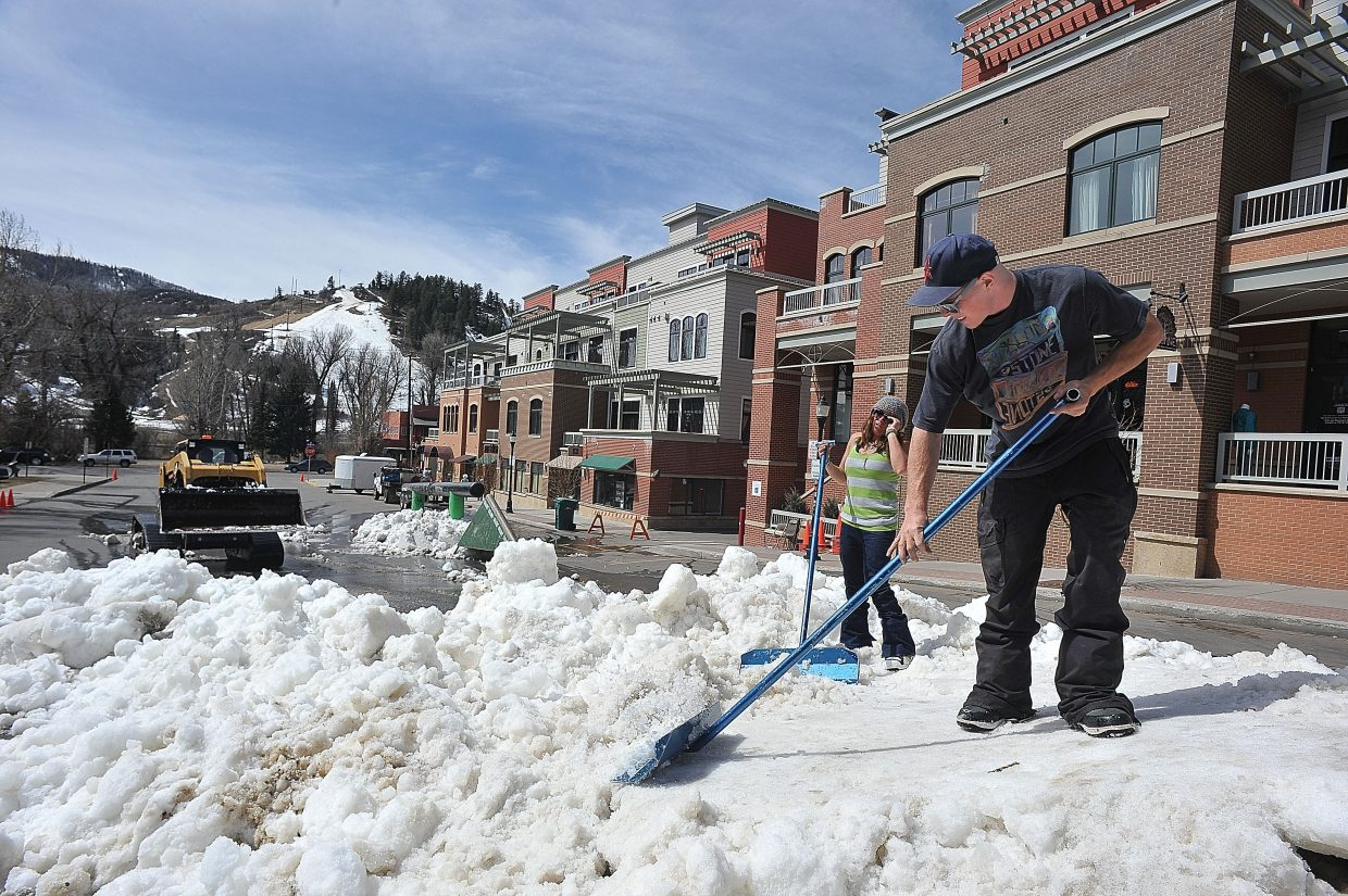 Brandon Harrison moves snow into place for the Urbane Midtown Crisis Rail Jam, which took place Friday evening on Seventh Street in downtown Steamboat Springs. Workers from Urbane, Powder Tools and Steamboat Ski Area moved snow to the location from Howelsen Hill.