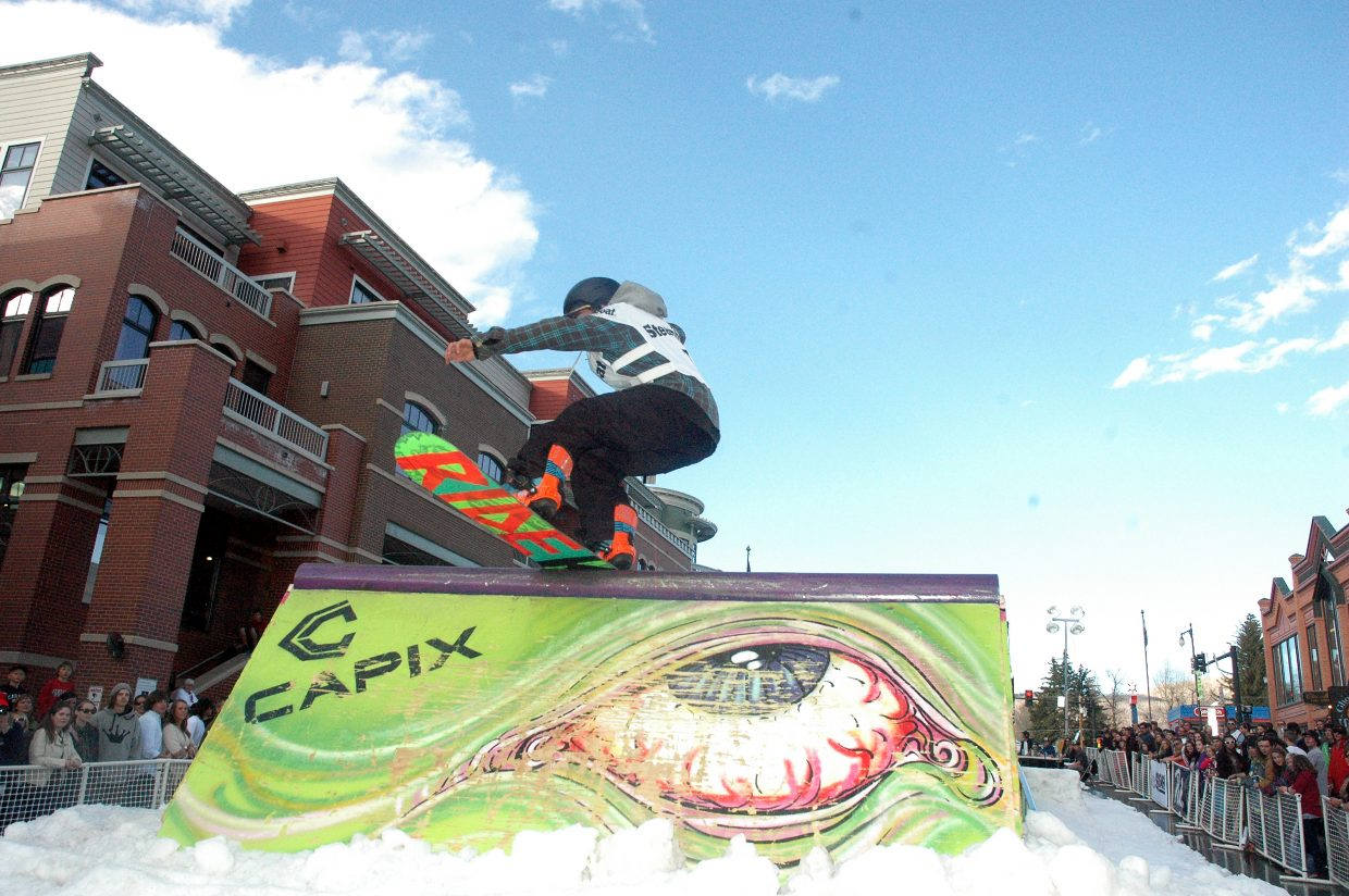 Snowboarder Kyle Kelley hits the wall ride feature at Friday evening's Urbane Midtown Crisis Rail Jam in downtown Steamboat Springs.