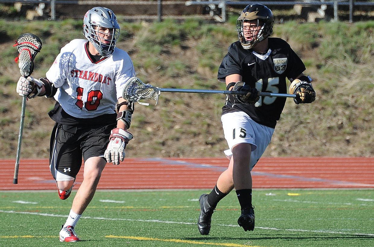 Battle Mountain's Sawyer Bluhm tries to poke at Steamboat's Ben Wharton on Friday in Steamboat Springs. The Sailors won the lacrosse game, 8-5.