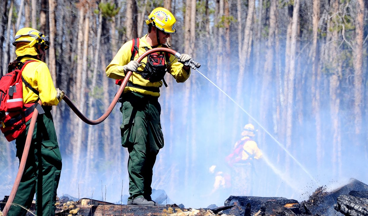 Oak Creek firefighter Kriss Bergethon targets some smoldering land with a water hose Friday while fighting fire in south Routt County. A downed power line sparked a fire. It turned out to be small, but with dry conditions, plenty of available fuel, the potential was there for a much larger event.